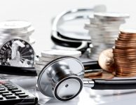 @Glowimages: Financial health concept, stethoscope weaving around stacks of silver and gold coins and calculator